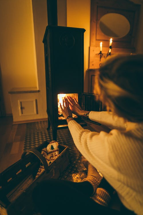 Woman Wearing White Long-sleeved Try to Get Heat at Fireplace
