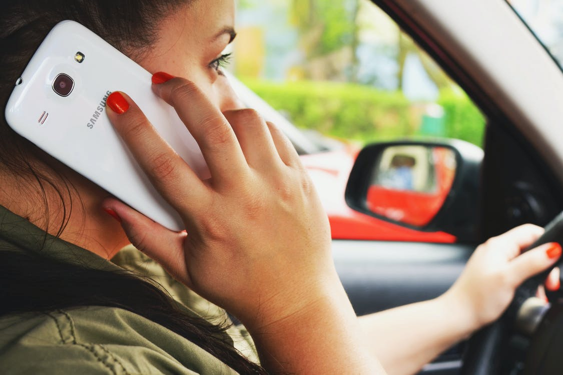 Woman Driving Car While Calling on Smartphone
