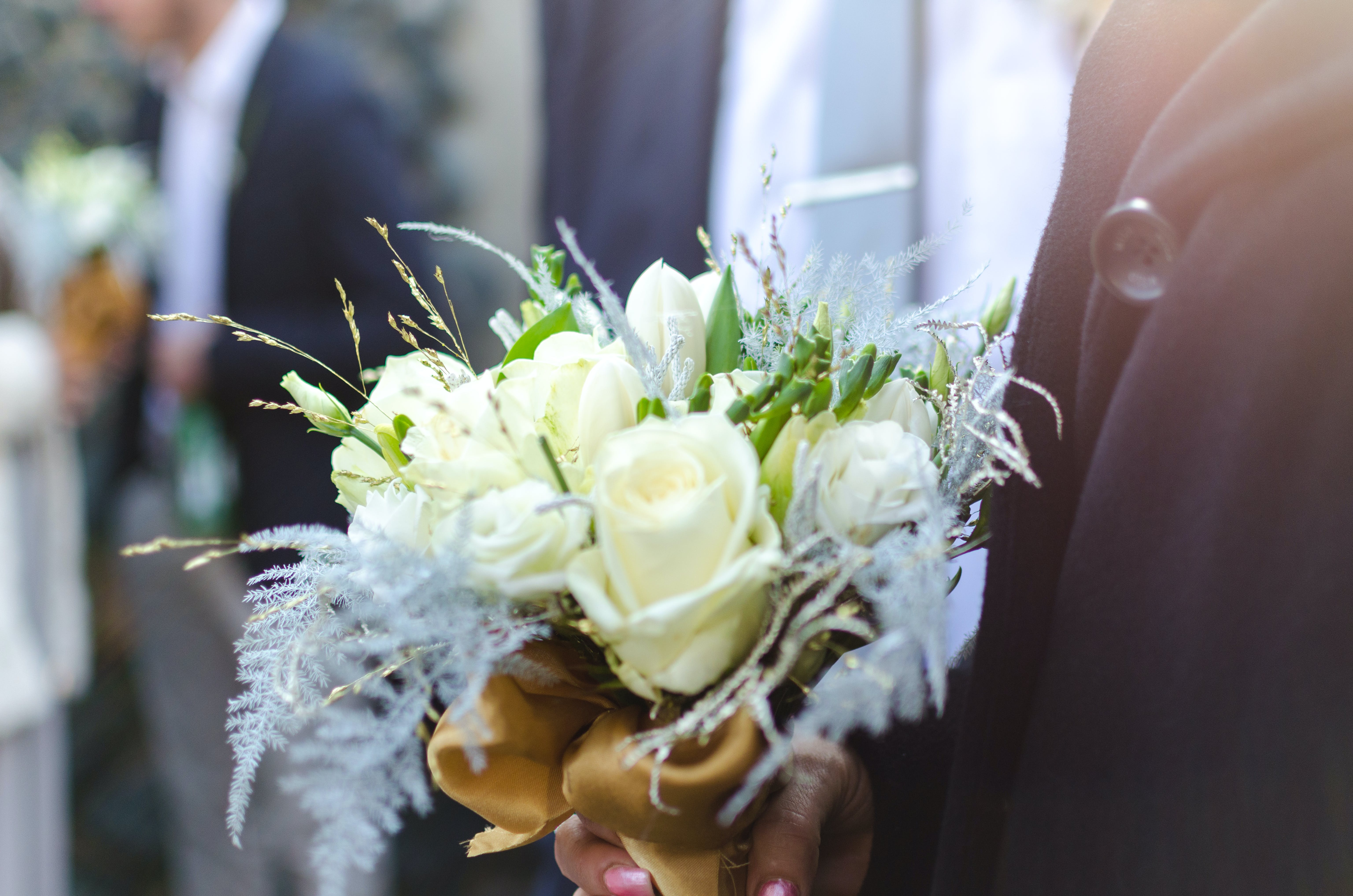 Person Holding Bouquet of White Roses