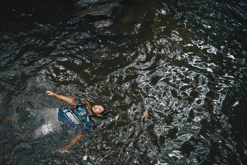 High-Angle Photo of Man Floating on Water
