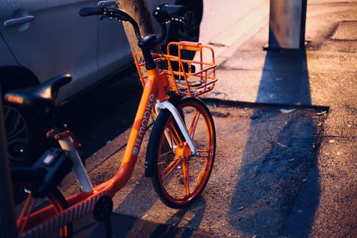 Photo of Orange Bicycle Parked on Pavement