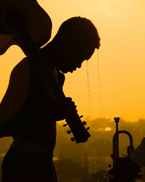 Silhouette Photo of Person Carrying Guitar