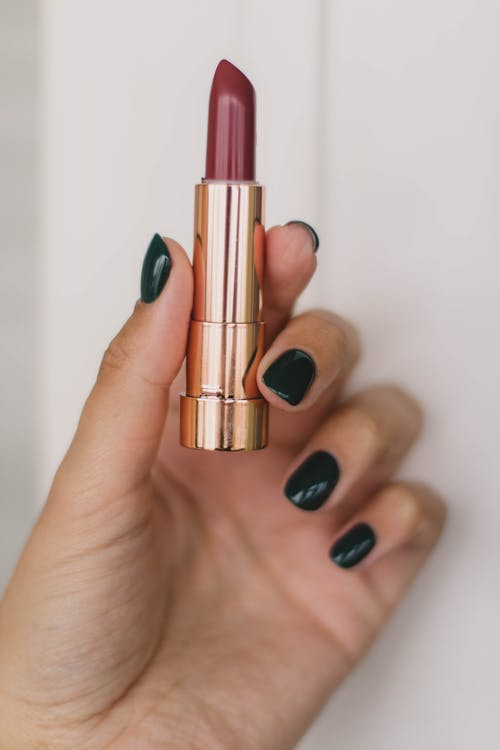 Close-Up Photo Of Person Holding Lipstick