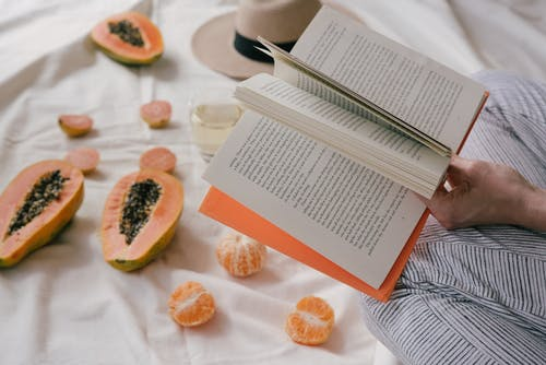 Opened Book And Sliced Papaya Fruit