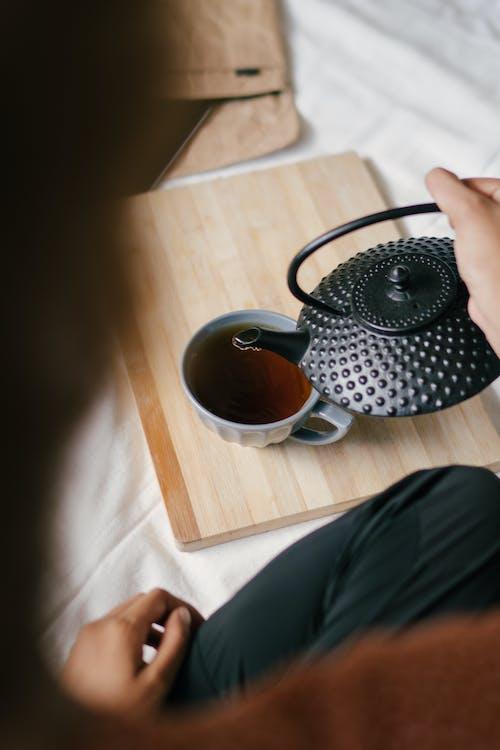 Person Holding Black Teapot