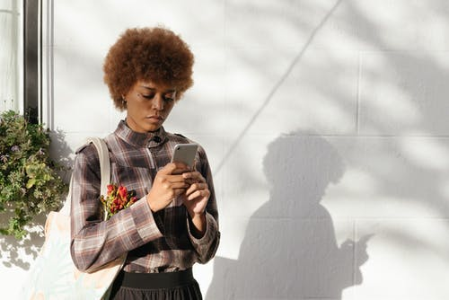 Woman Wearing Plaid Shirt And Looking At Her Phone