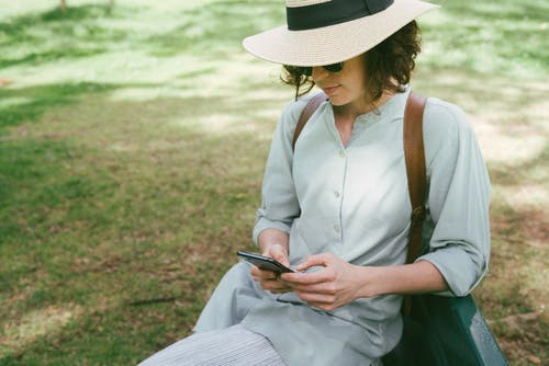 Woman Wearing Fedora Hat Sitting On Grass