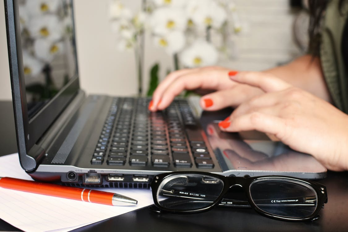 Woman in Front of Laptop Beside White Moth Orchids
