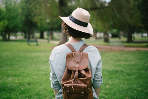 Photo of Woman Wearing Sun Hat and Leather Bag
