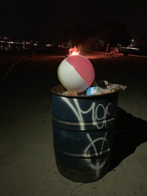 Garbage container filled with rubbish and beach ball placed on coast against burning campfire