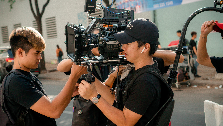 Photo Of Men Holding Camera