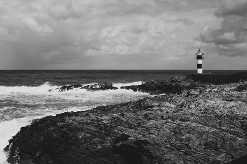Grayscale Photo of Lighthouse on Seashore