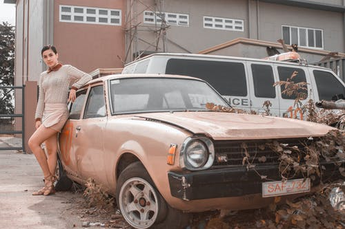 Woman Posing Beside An Abandoned Car