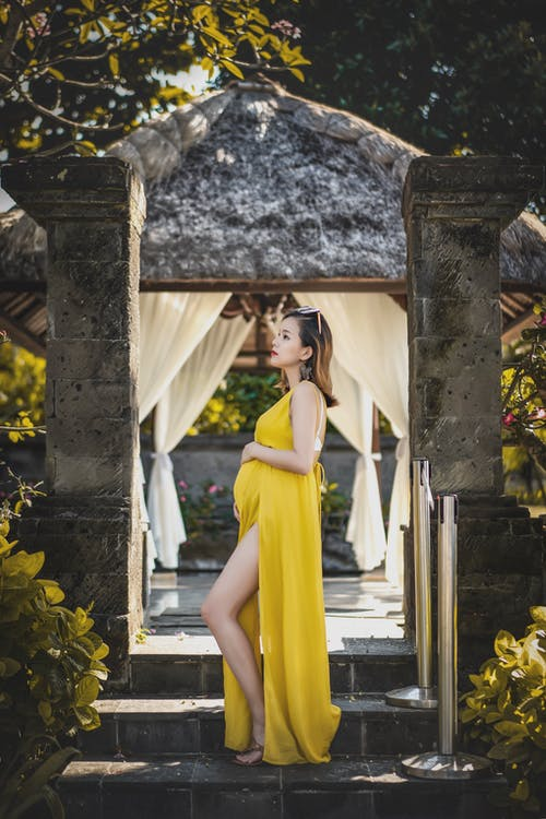 Woman Wearing Yellow Dress While Standing on Stairway