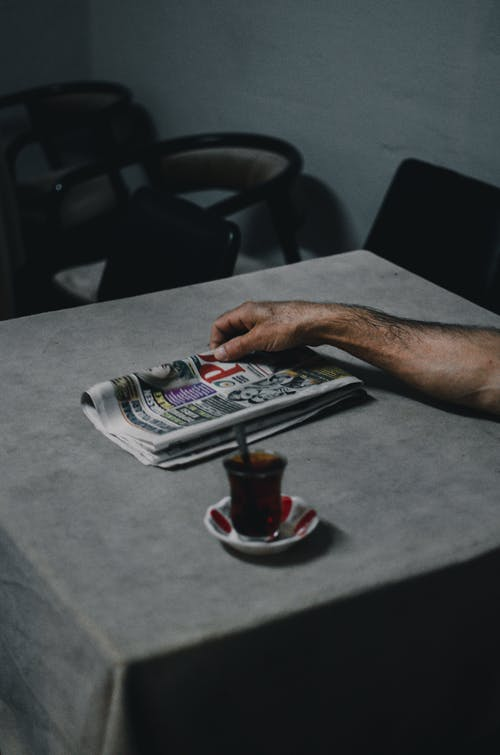 Person Holding Newspaper on Table
