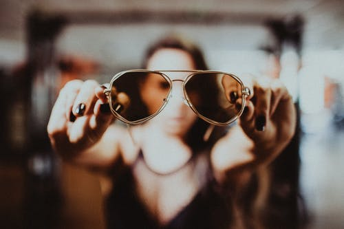 Shallow Focus Photo of Person's Hand Holding Sunglasses
