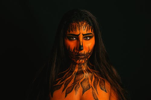 Woman With Face and Body Paint Against Black Background