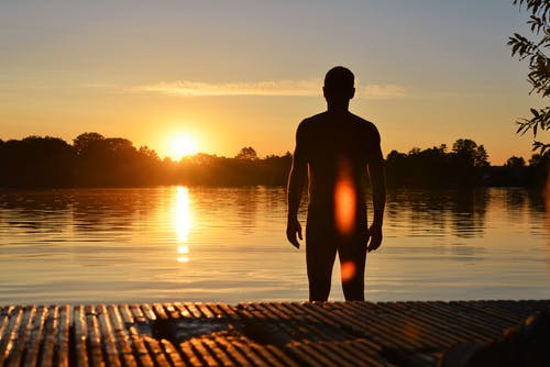 Silhouette Photo of Man Standing Near Lake