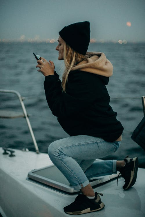 Woman Wearing Black Hoodie While Using Smartphone