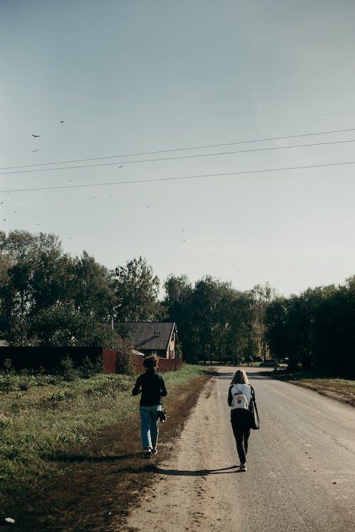 Two Women Walking on Road