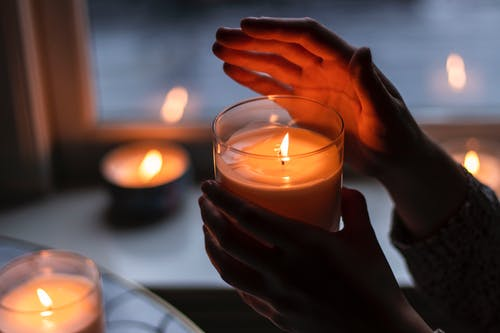 Photo of Person Holding Scented Candle