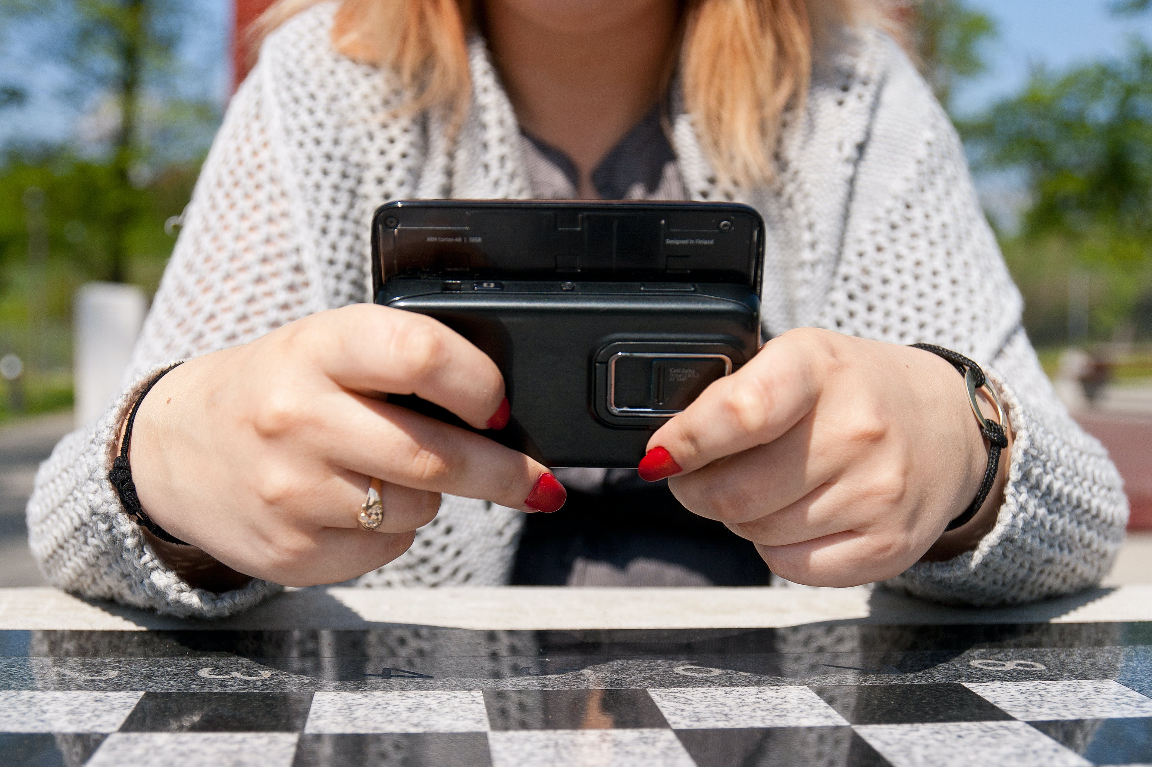 Person Holding Slide Qwerty Phone While Leaning on Table