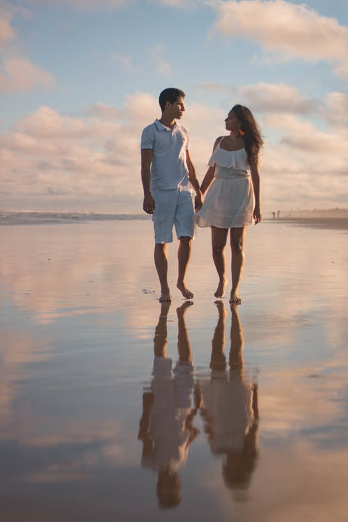 Couple Walking Along The Shore