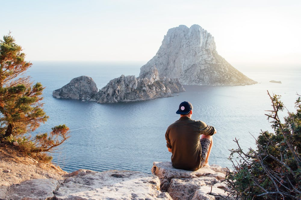 A man sitting on the rock. | Photo: Pexels