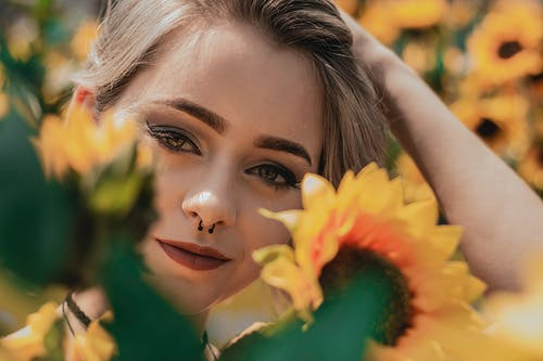Close-up Photo of Smiling Woman Posing by Yellow Sunflowers