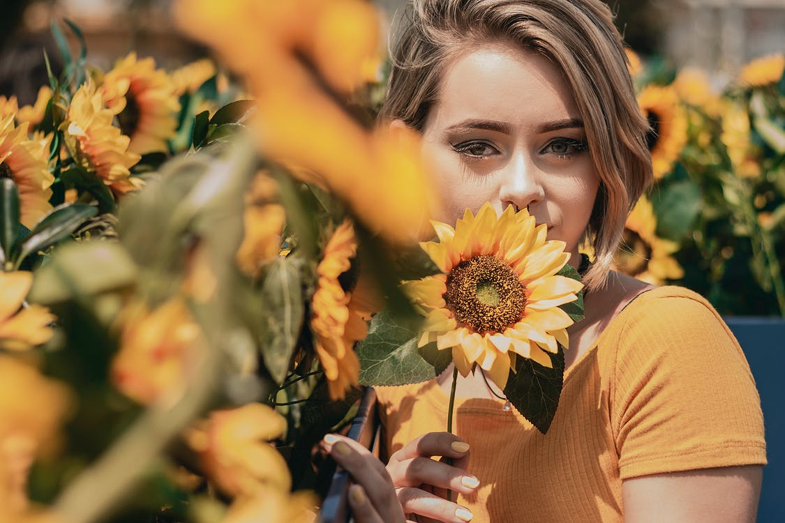 Portrait Photo of Woman in Yellow Top Posing Near Sunflowers