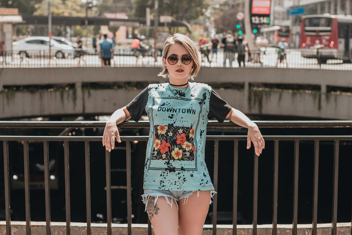Photo of Woman in Sunglasses, T-shirt, and Denim Shorts Leaning on Metal Railing Posing