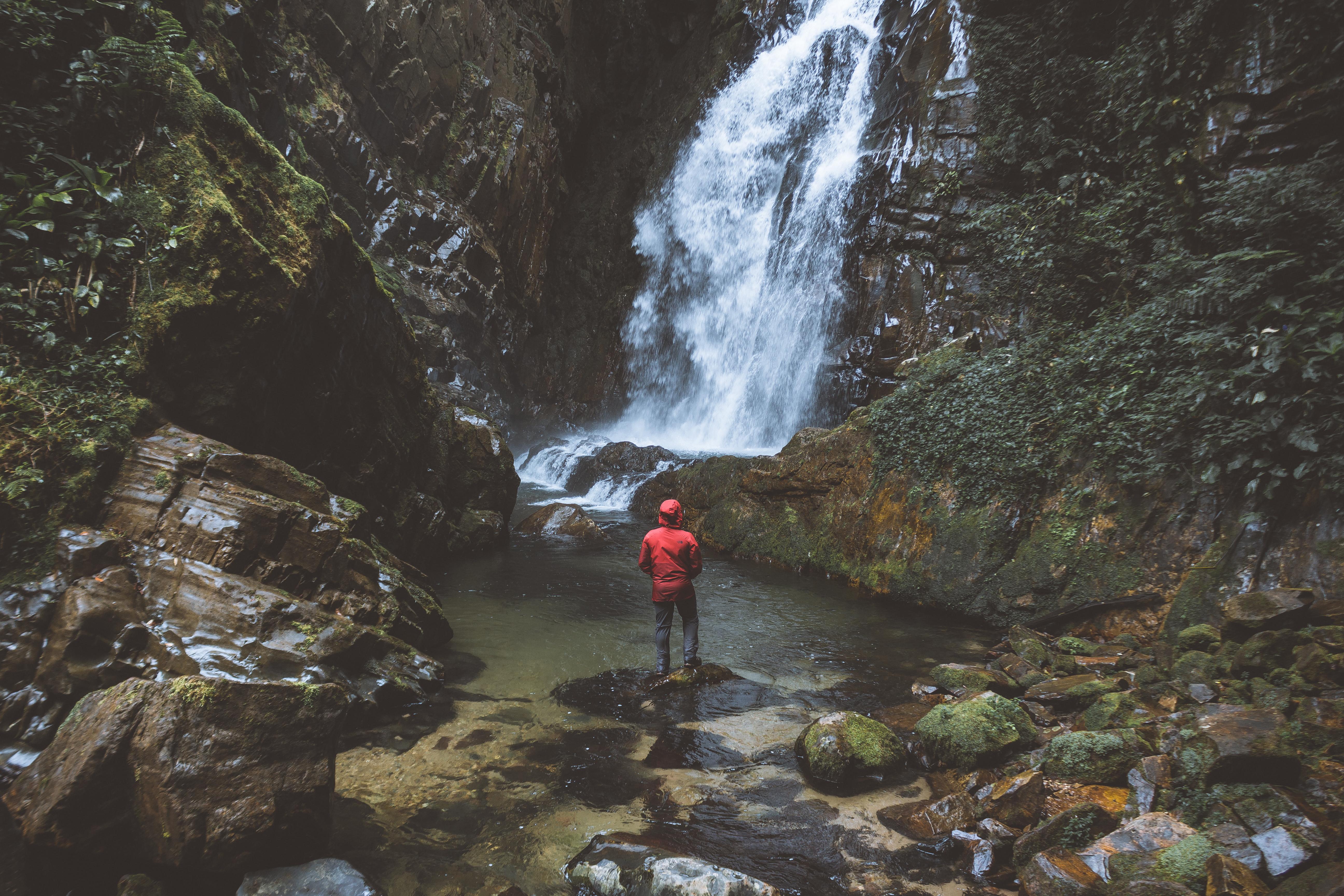 Person Standing Beside Waterfalls