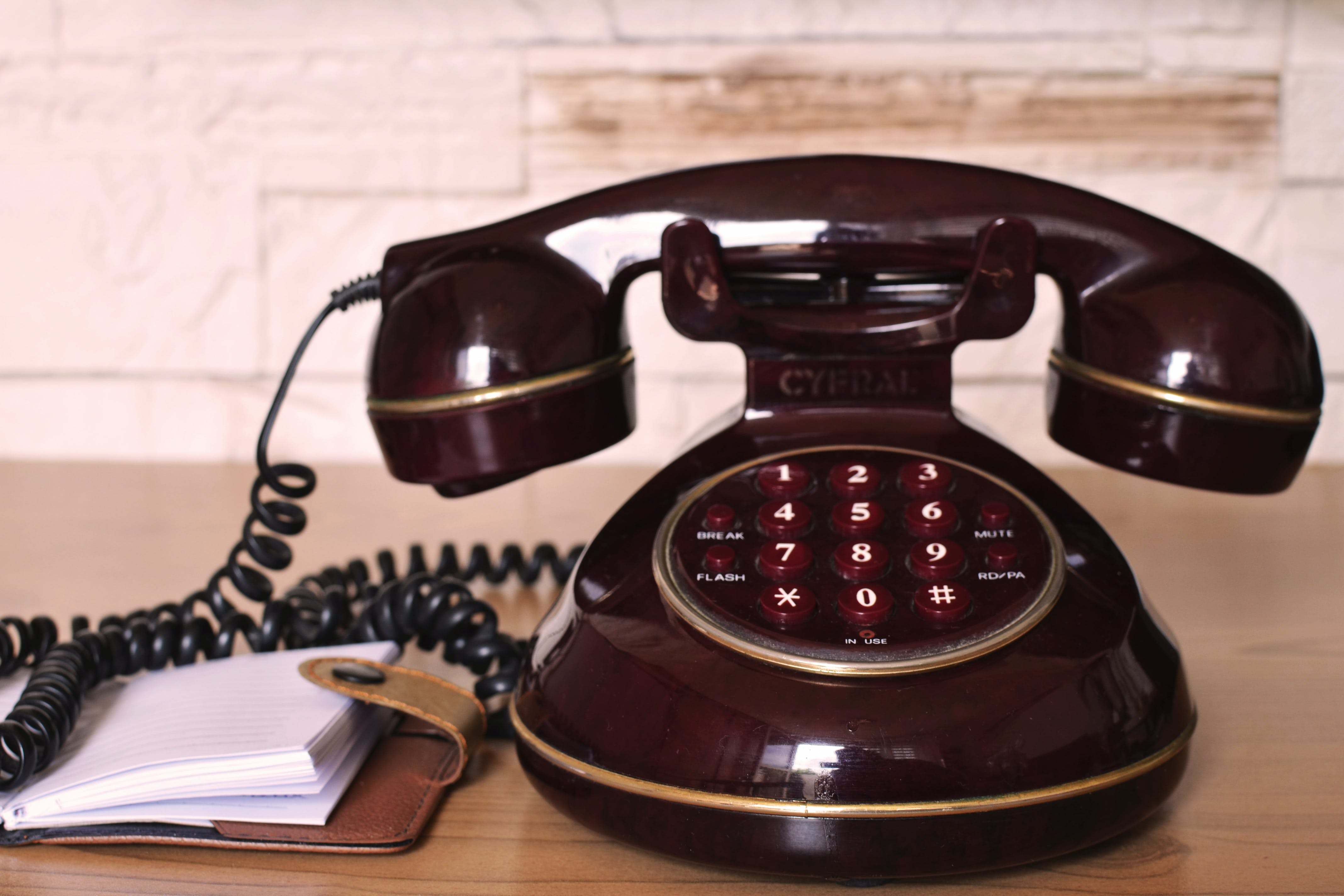 Maroon Push Button Telephone on Table