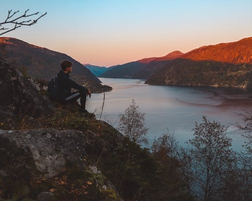 Man Sitting on Cliff Facing Calm Body of Water
