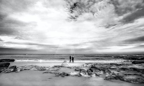 Two People Standing on Seashore
