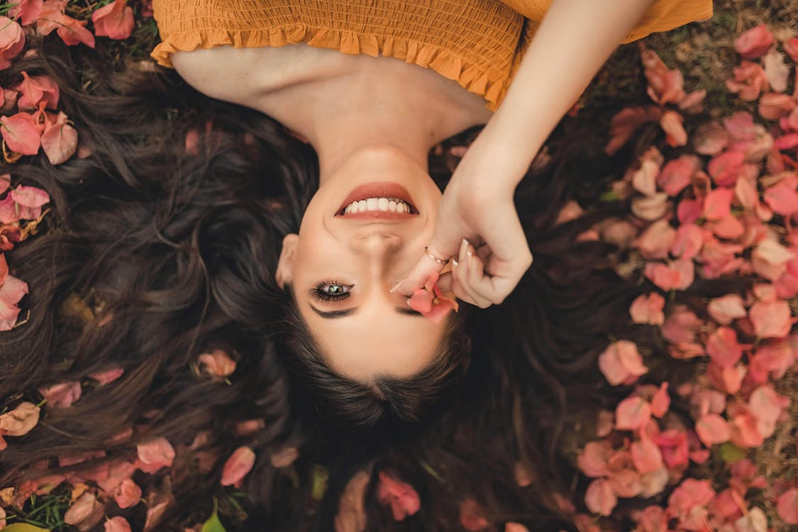 Photo Of Woman Laying On Petals