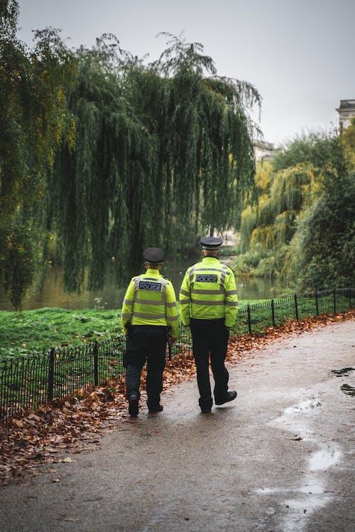 2 Securities Walking Beside Dried Leaves