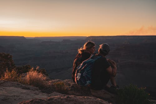 Man and Woman Sitting on Mountain Edge