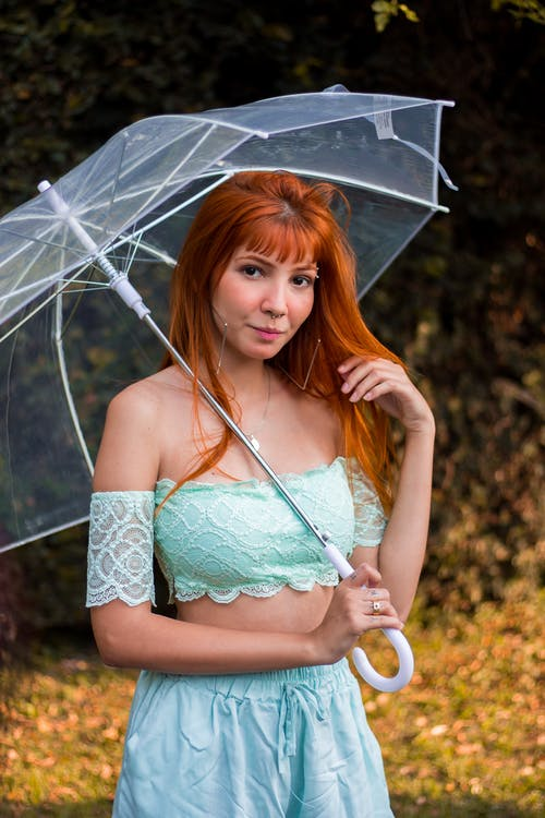 Selective Focus Photo of Woman Holding Clear Umbrella Posing