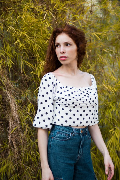 Photo of Woman in Polka-dot Top and Blue Jeans Posing While Looking Away