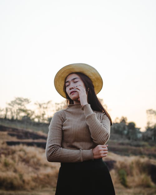 Photo of Woman in Brown Sweater, Black Dress, and Sun Hat Posing With Her Eyes Closed