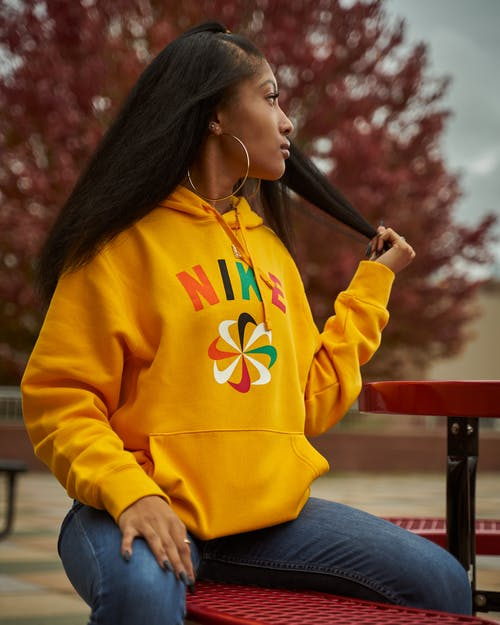 Selective Focus Photo of Woman in Yellow Hoodie and Blue Jeans Sitting on Red Bench While Looking Away