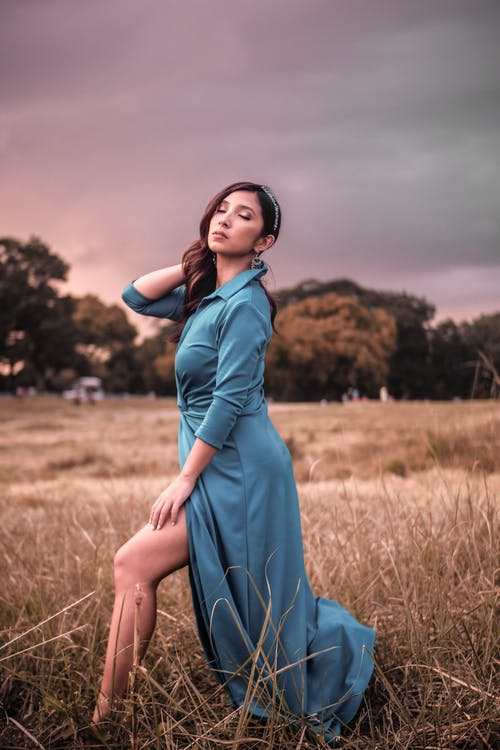 Photo of Woman in Blue Dress Posing With Her Eyes Closed