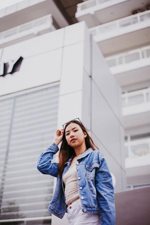 背景に建物とポーズをとって青いデニムジャケットの女性の写真