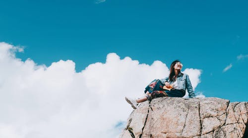 Woman Wearing Blue Denim Jacket Sitting on Top of A Rock