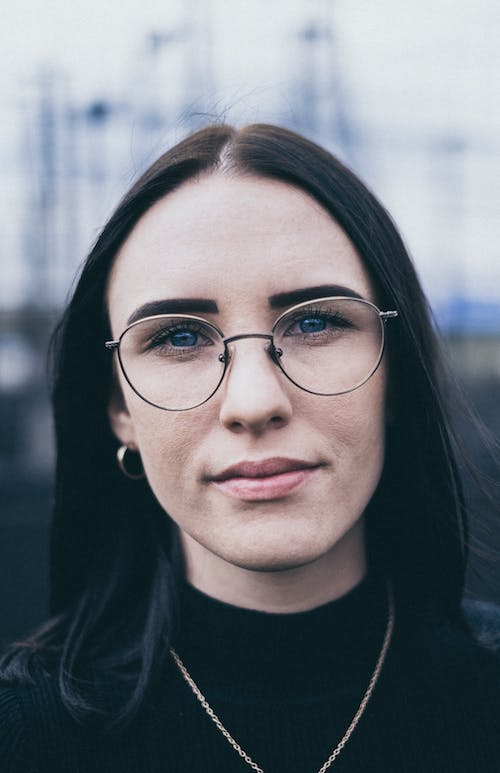 Selective Focus Portrait Photo of Woman in Glasses and Black Top Posing