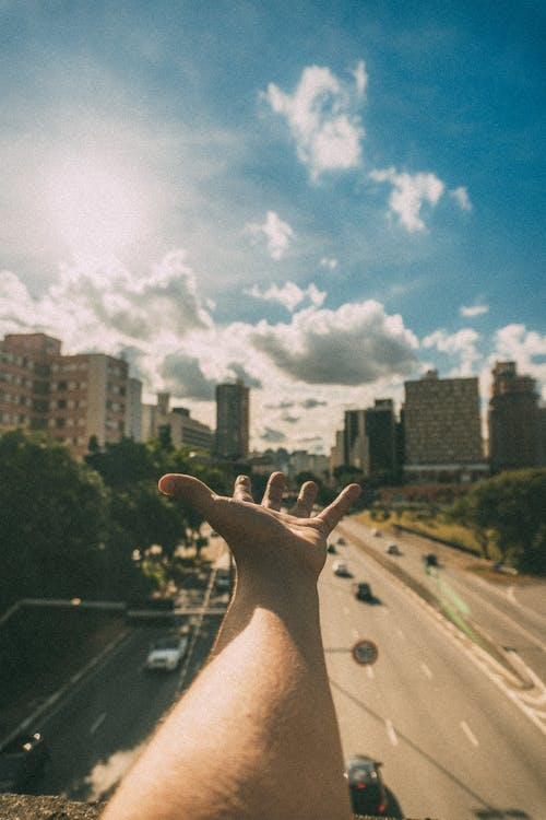 Person's Hand Near High-rise Buildings