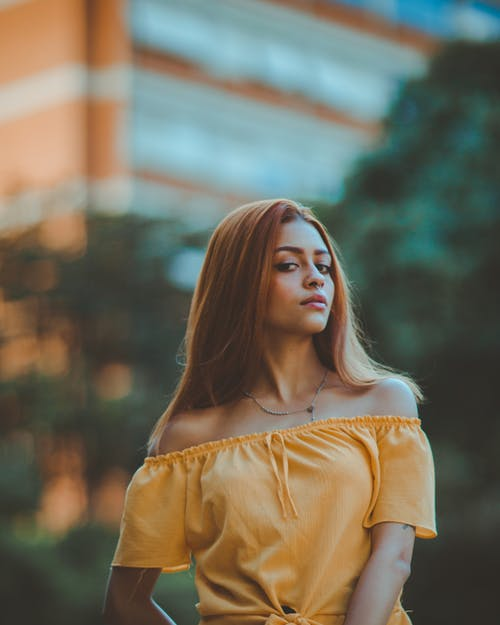 Selective Focus Photo of Woman in Yellow Off-shoulder Top Posing