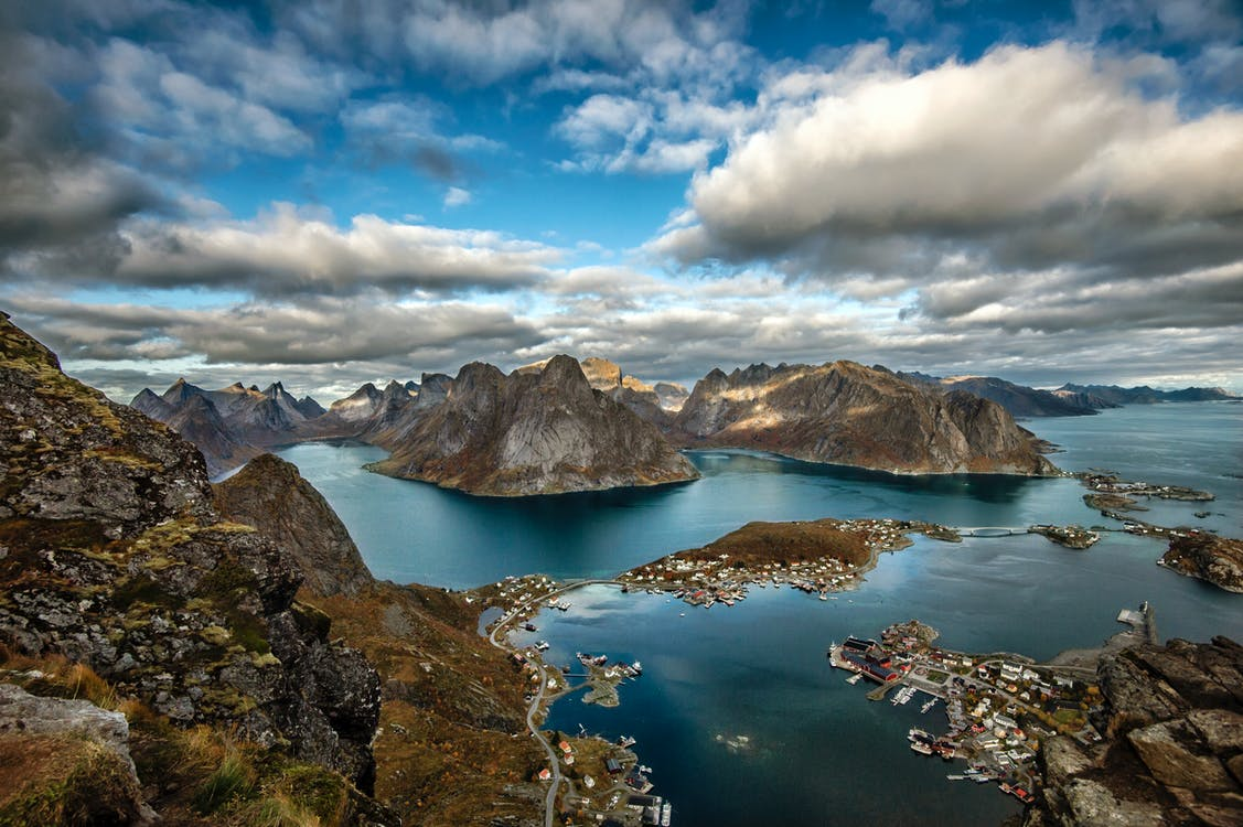 Landscape Photography of Mountains Surrounded by Water