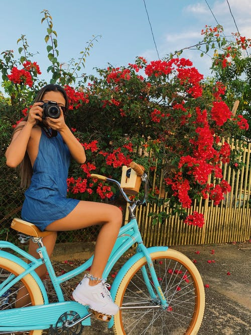 Woman Seated on Bike Using Camera